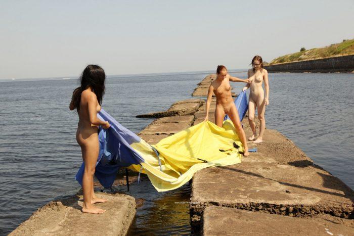 Three sexy sailors posing naked at stone pier