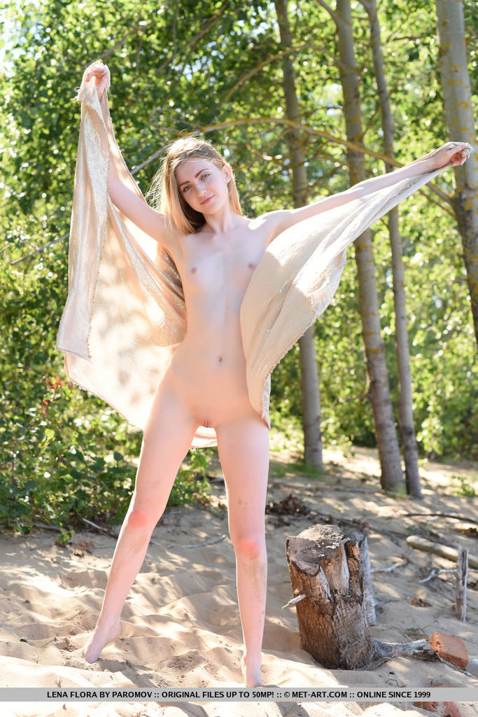 Youthful Lena Flora poses on the sand baring her creamy, nubile body.