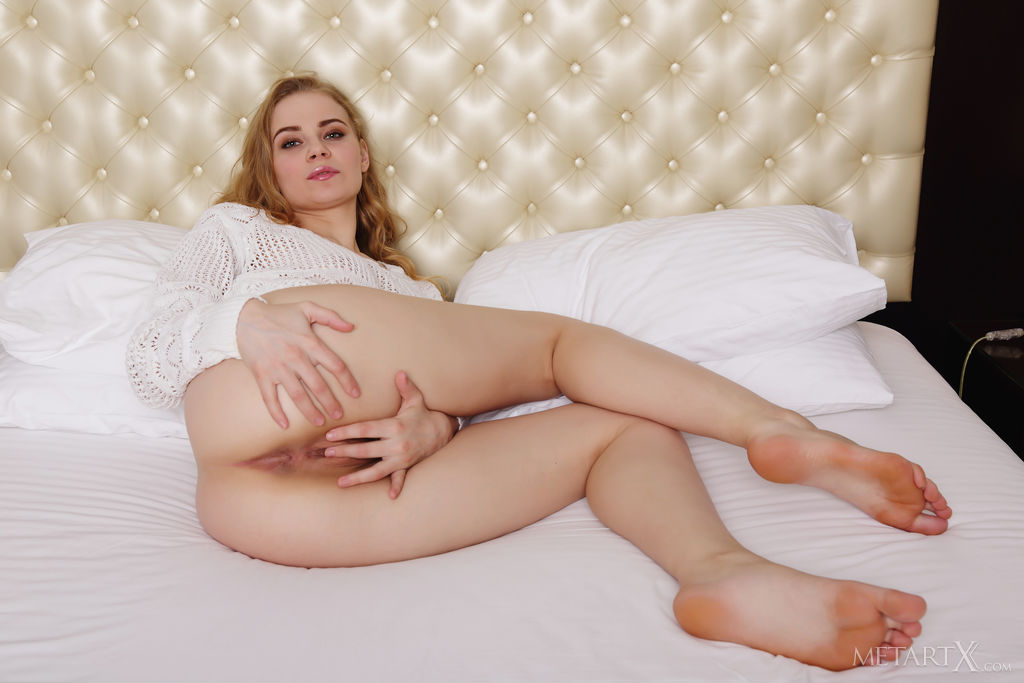 Ellie lays invitingly on the white bed and she slowly peels off her clothing and showcase her naked body