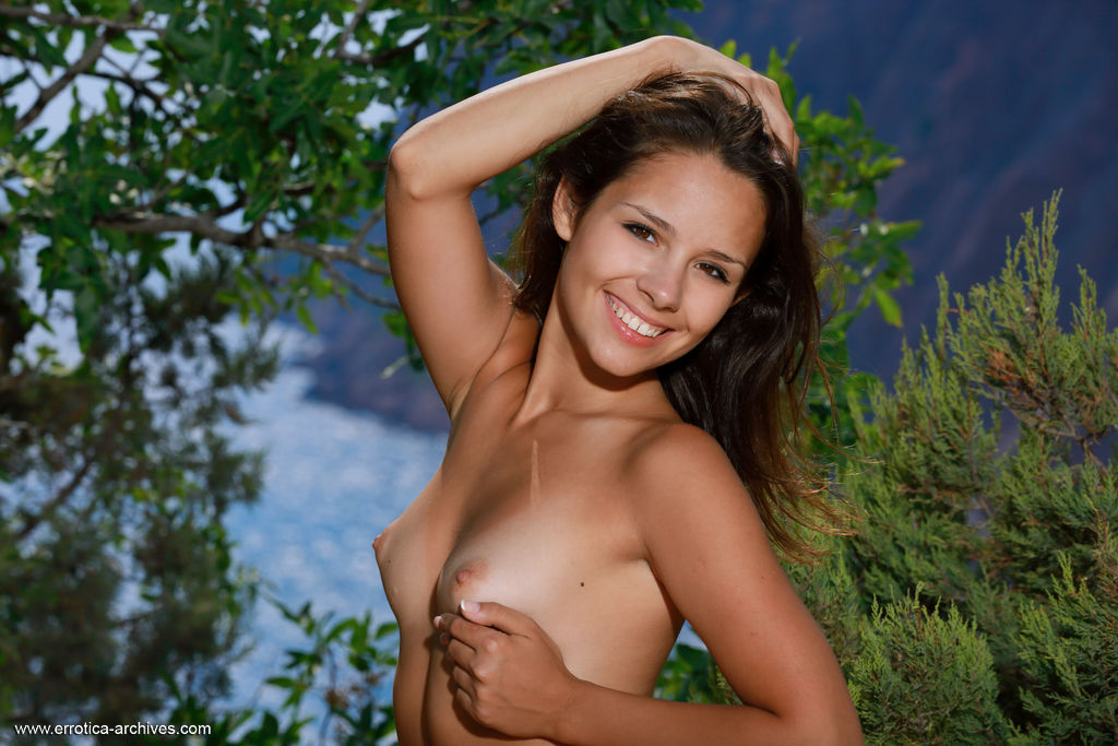 Emmy displays her tanned body and sweet pussy as she poses outdoors.