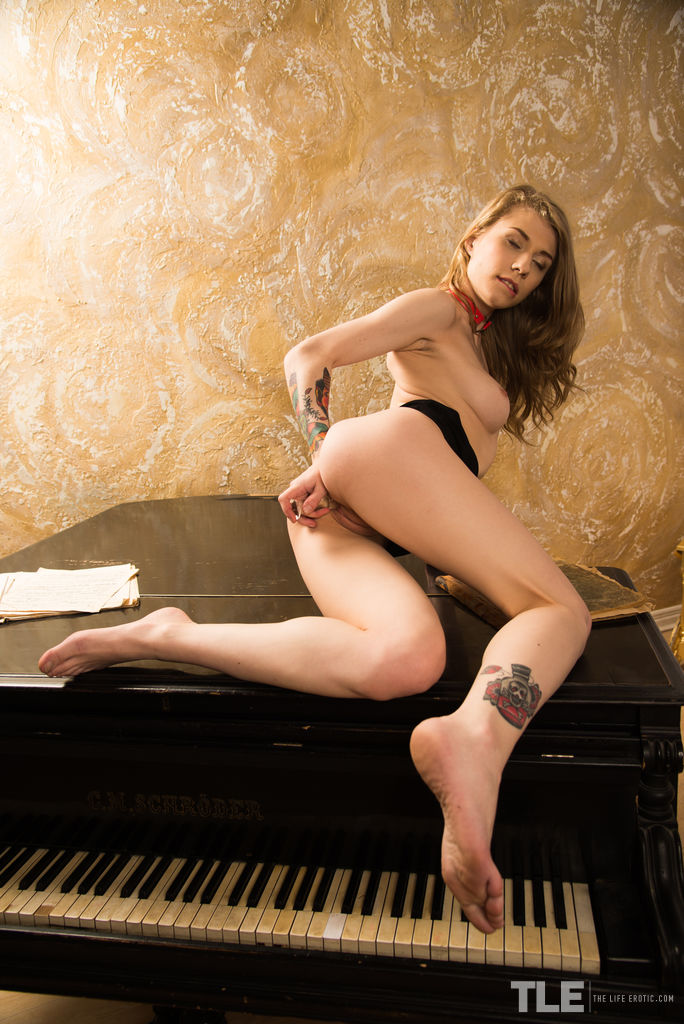 Eva Gold hops up on the grand piano as she plunges the toy deep into her creaming snatch.