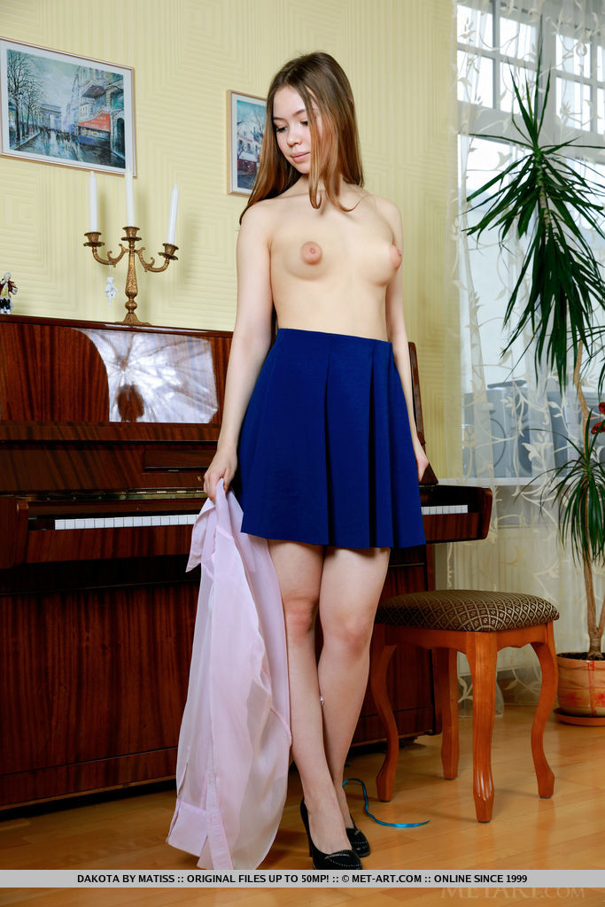 School girl Dakota displays her nubile body as she strips on the piano.