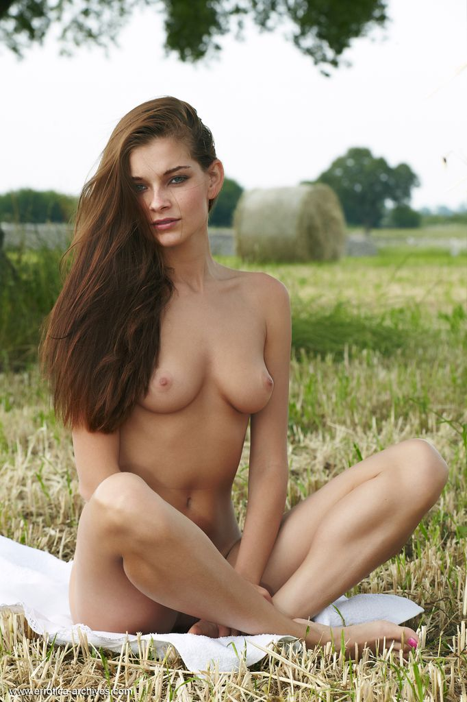 Belle lays in the grass and shows off her incredibly tight body.