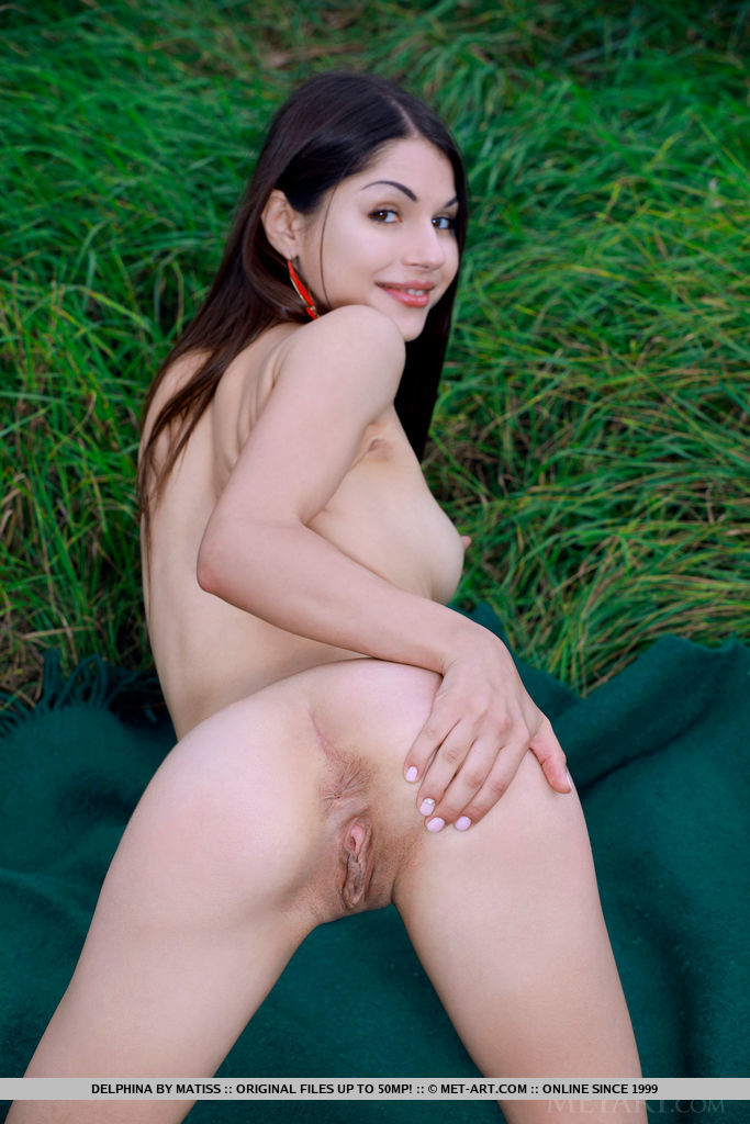 Delphina delightfully poses on the grass as she strips her red bikini baring her shaved pussy.