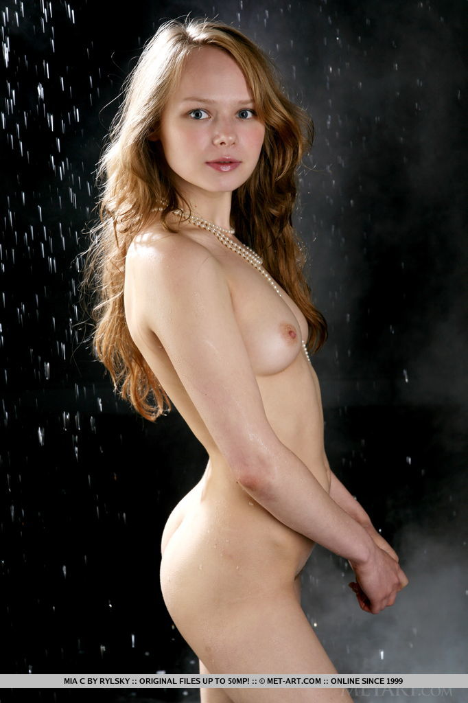 Mia C glistening in the darkness, her small perky breasts and unshaved pussy