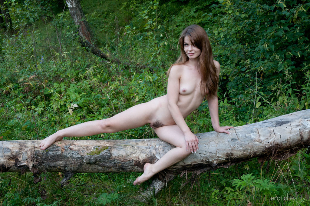 Nedda A strips in the woods as she bares her trimmed pussy.