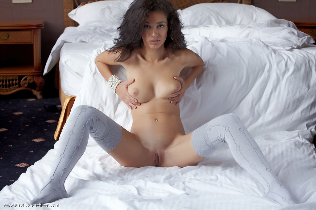 Sexy Karen lazes near a white bed and shows off her curvy ass and tight slit.