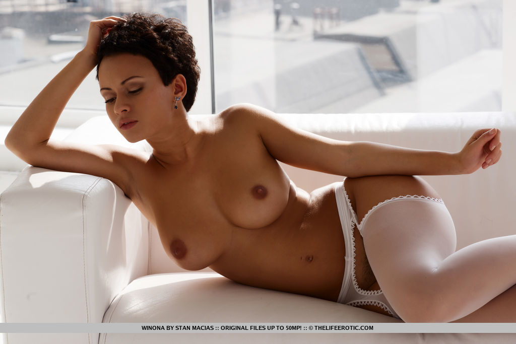 Winona showcases her stunning body with luscious full breasts and untrimmed labia by the window.