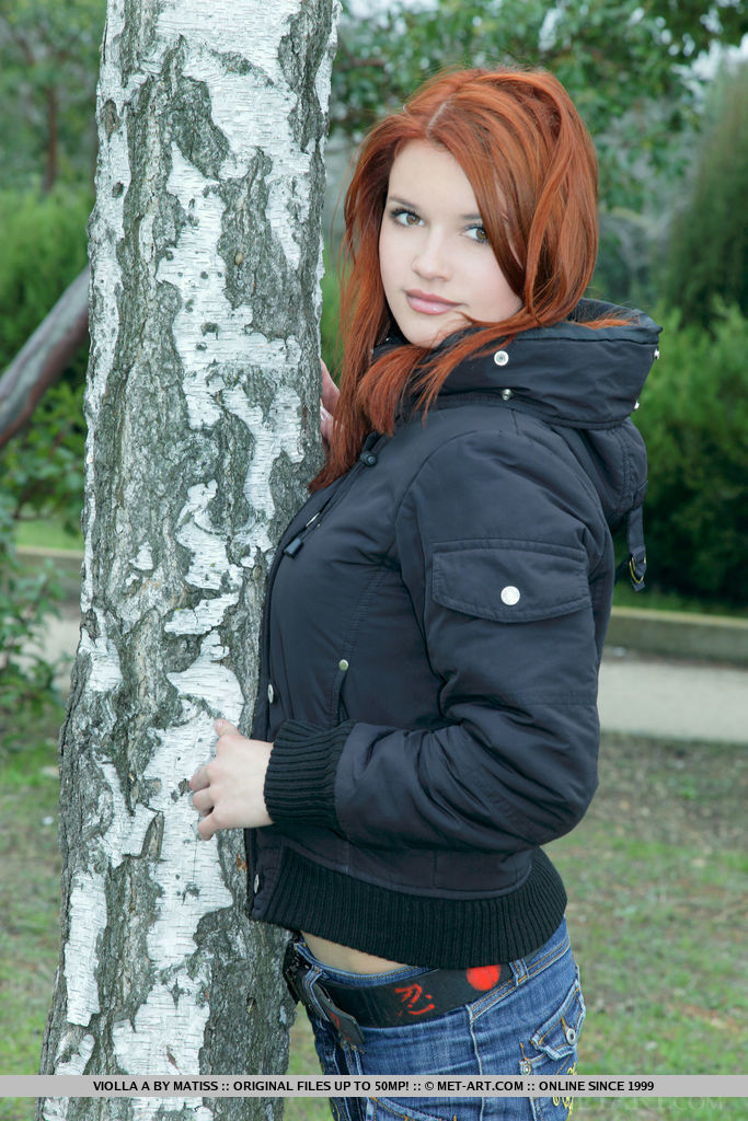 Redhead Violla A displays her sexy, curvy body and smooth pussy in the jungle.
