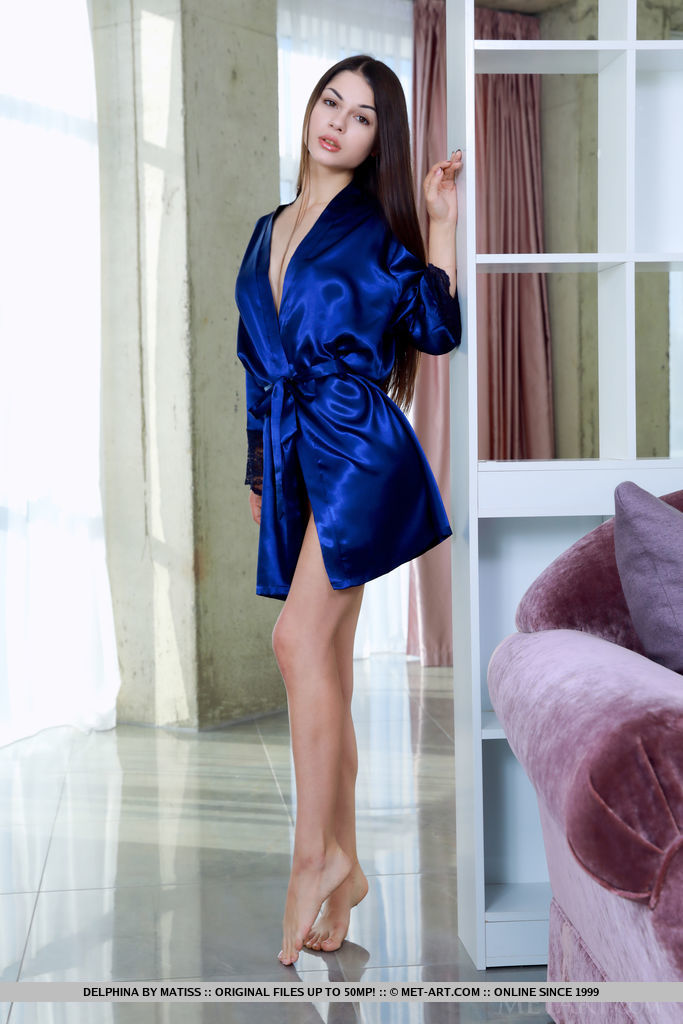 Delphina takes off her blue silk robe. She lays her slender body on the bed.