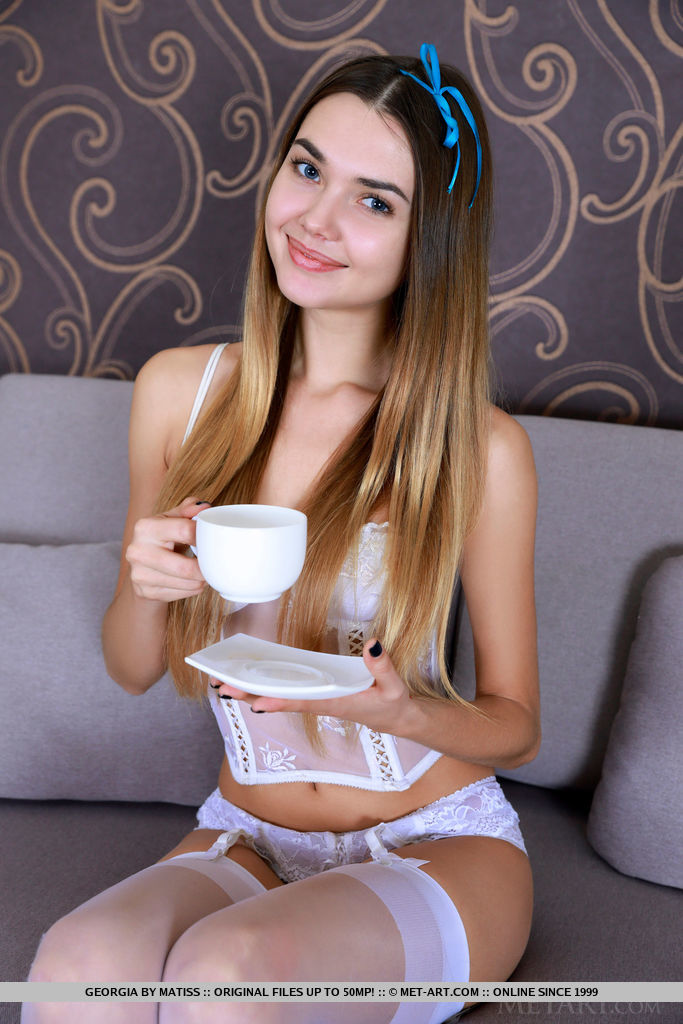 Georgia is both sexy and cute in her white lingerie and stockings. She goes nude on the couch showing her slim body.