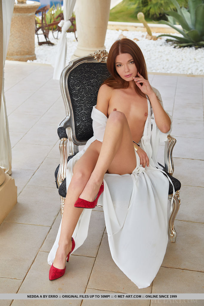 Nedda A bares her sweet, pink cunt as she poses on the chair with her red stilettos.