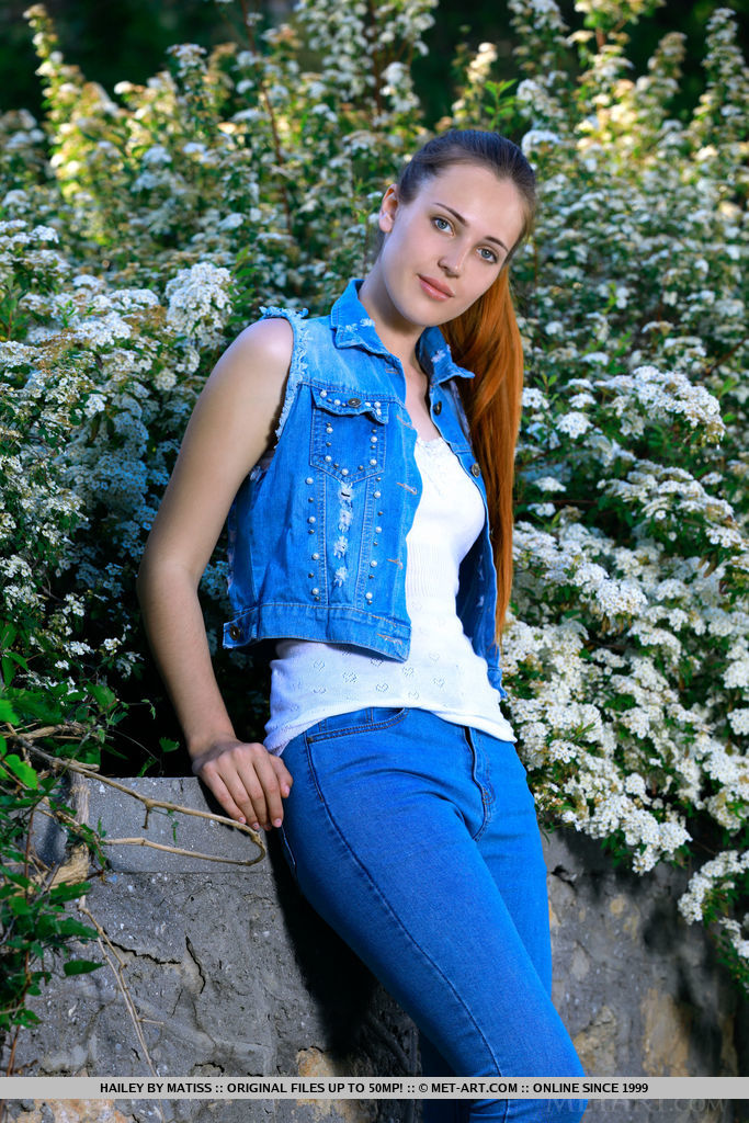 Hailey looks beautiful in a ponytail. She takes of her jeans and denim top by the flower bed.