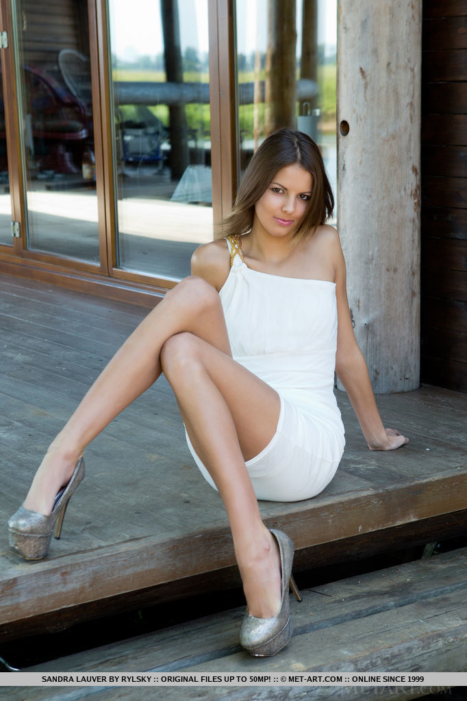 A body-hugging white dress and silver stiletto shoes show off Sandra Lauver long and slender physique and gorgeous legs.