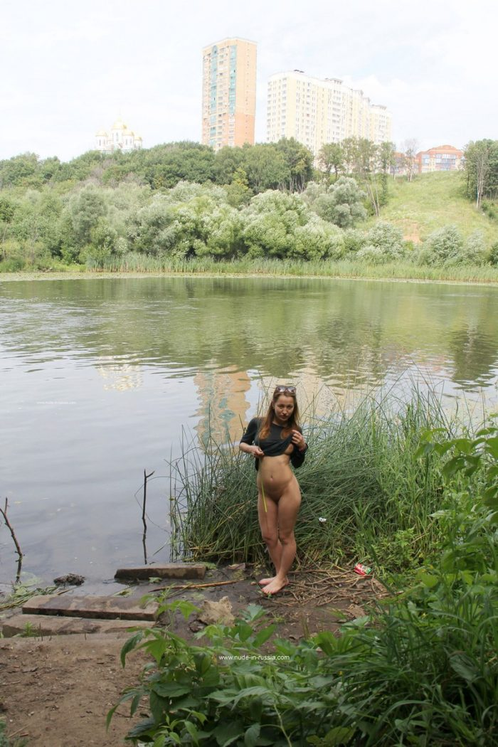 Busty girl Abbey undresses by the lake
