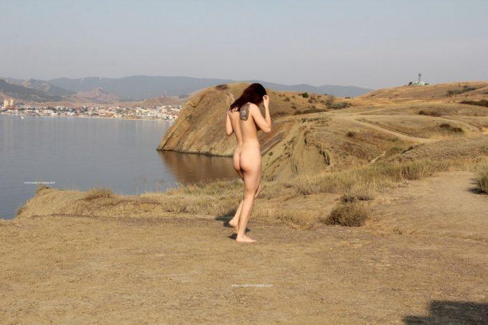 Adolescente ruiva caminha nua no ponto de vista