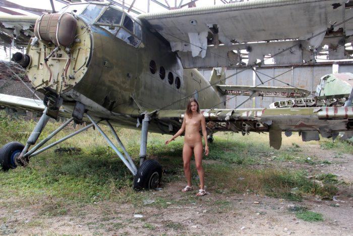 Olga W com tetas pequenas perto de aviões antigos