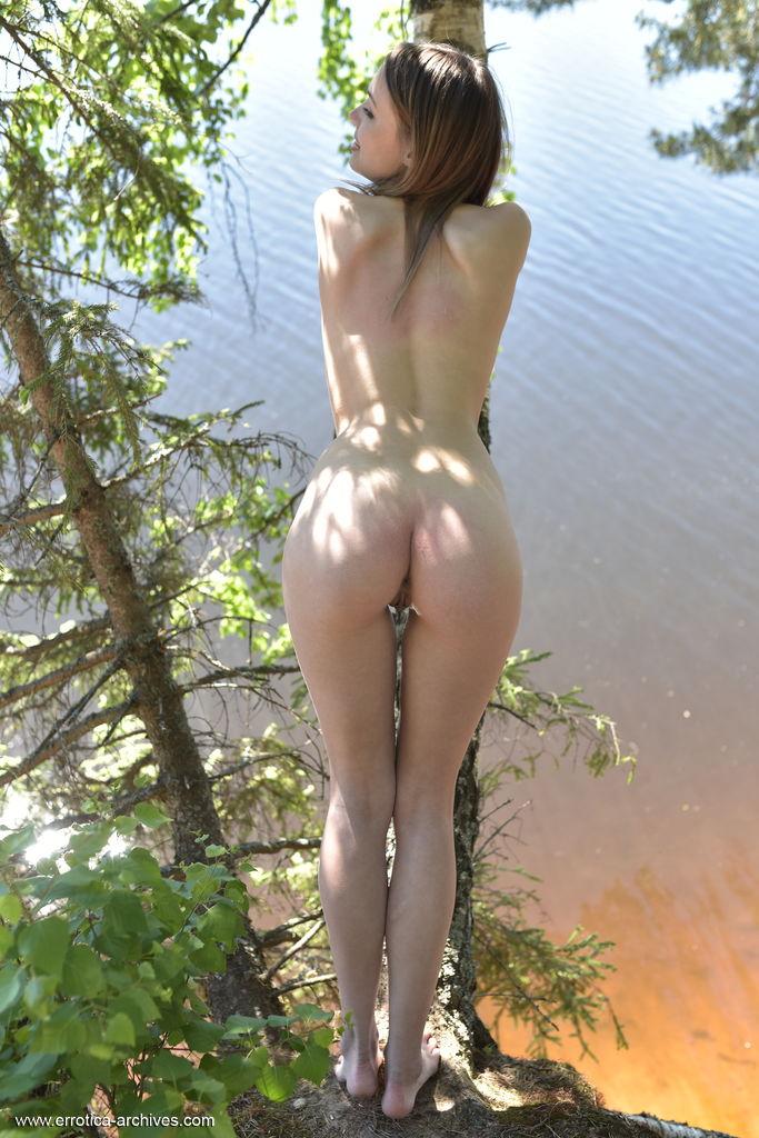 Maxa de cabelos lisos fica completamente nua ao ar livre e posa com a vegetação.
