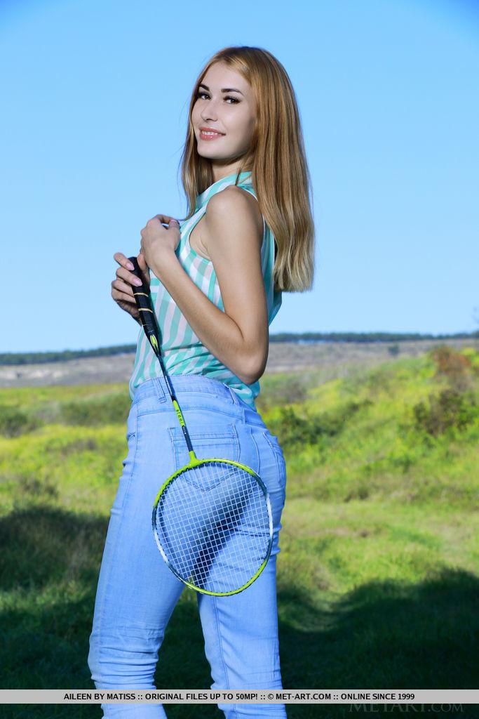Aileen está jogando badminton ao ar livre. Ela tira a roupa e coloca o corpo esbelto na grama.