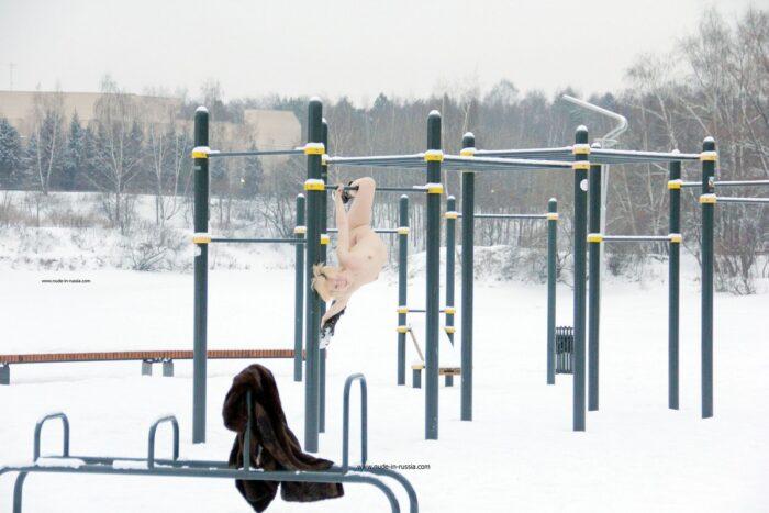 A loira de cabelos curtos Elena B faz ginástica ao ar livre no inverno