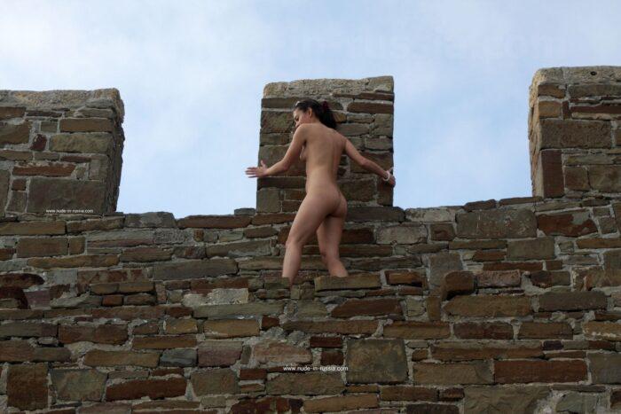 Menina Nasiba Z sem roupas na parede do castelo