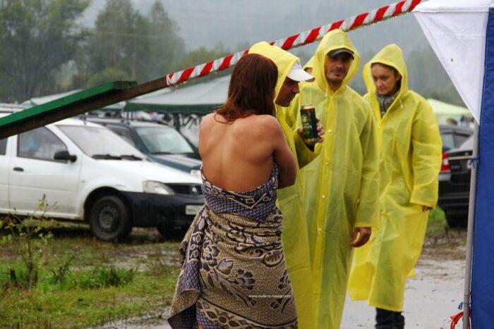 Garota ruiva andando nua na frente de estranhos na chuva