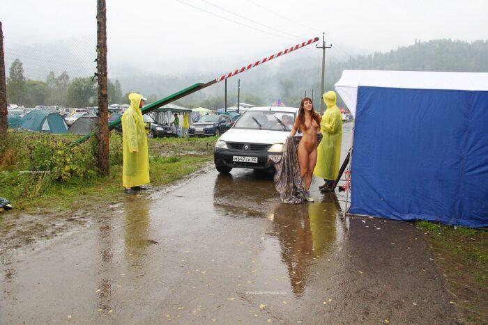 Garota ruiva caminhando nua na frente de estranhos na chuva