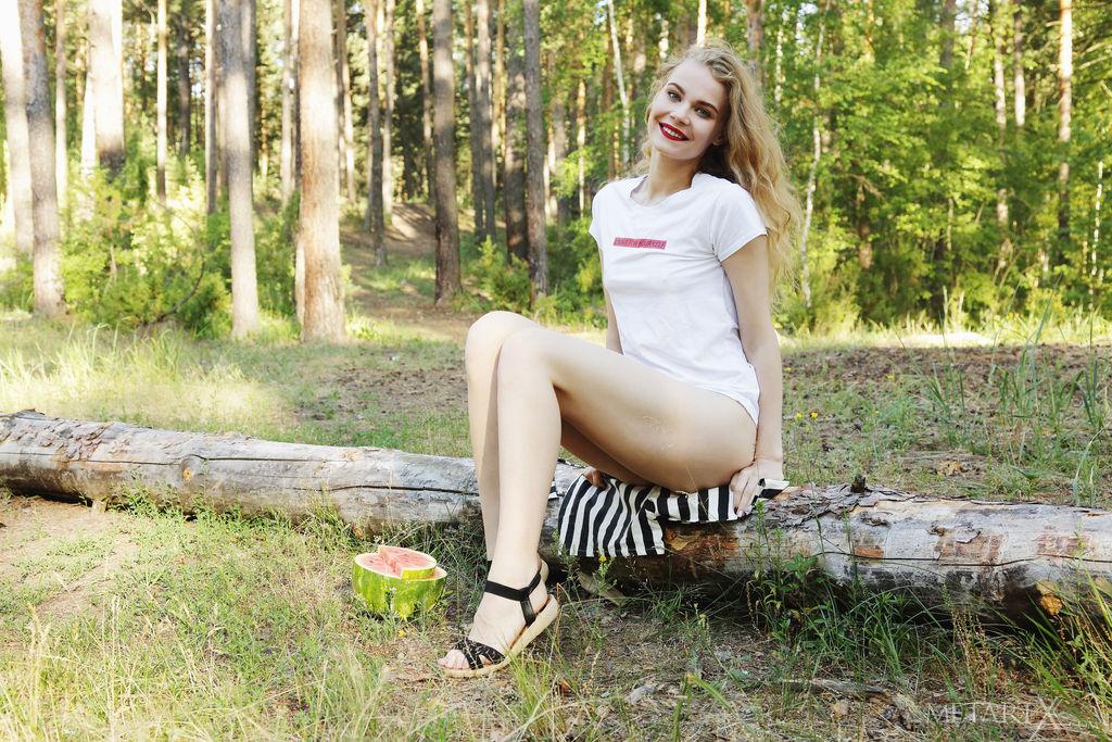 Ellie está na floresta, comendo uma melancia, tira o short listrado e se toca no tronco.