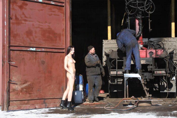 Garota russa nua Lera ao lado de reparadores de automóveis