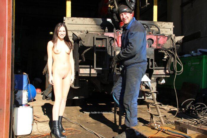 Garota russa nua Lera ao lado de mecânicos