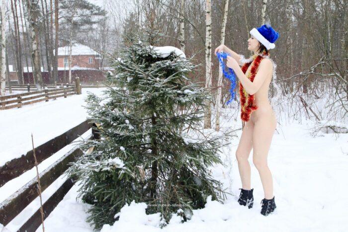 Lia A de cabelos curtos enfeita uma árvore de Natal na rua