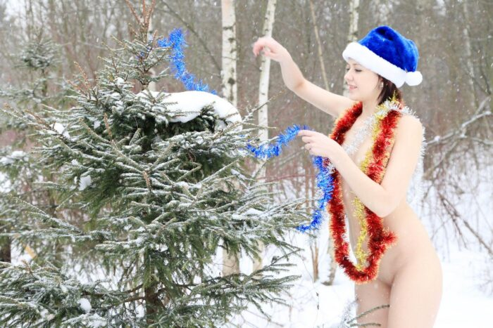 Lia A, de cabelos curtos, enfeita uma árvore de Natal na rua