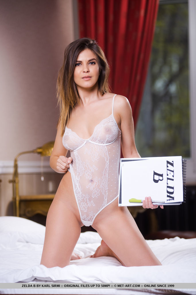 Zelda B takes off her white lace bodysuit on the bed then poses with the white sheets.