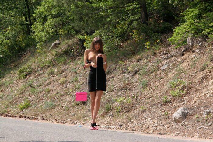 Menina Masha E com bolsa rosa em uma estrada na montanha