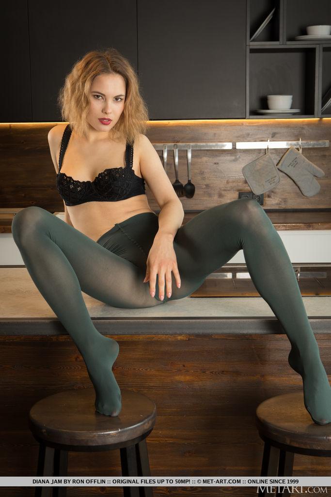 Diana Jam se delicia na cozinha em suas meias pretas transparentes enquanto sobe na mesa e fica nua.