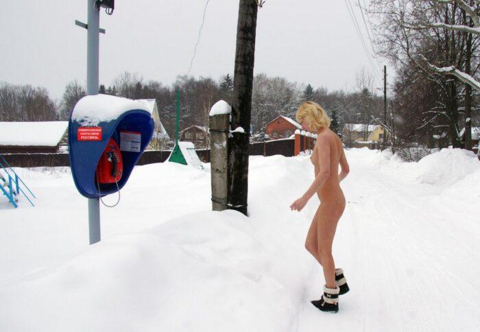 Diana nua falando em um telefone público no inverno