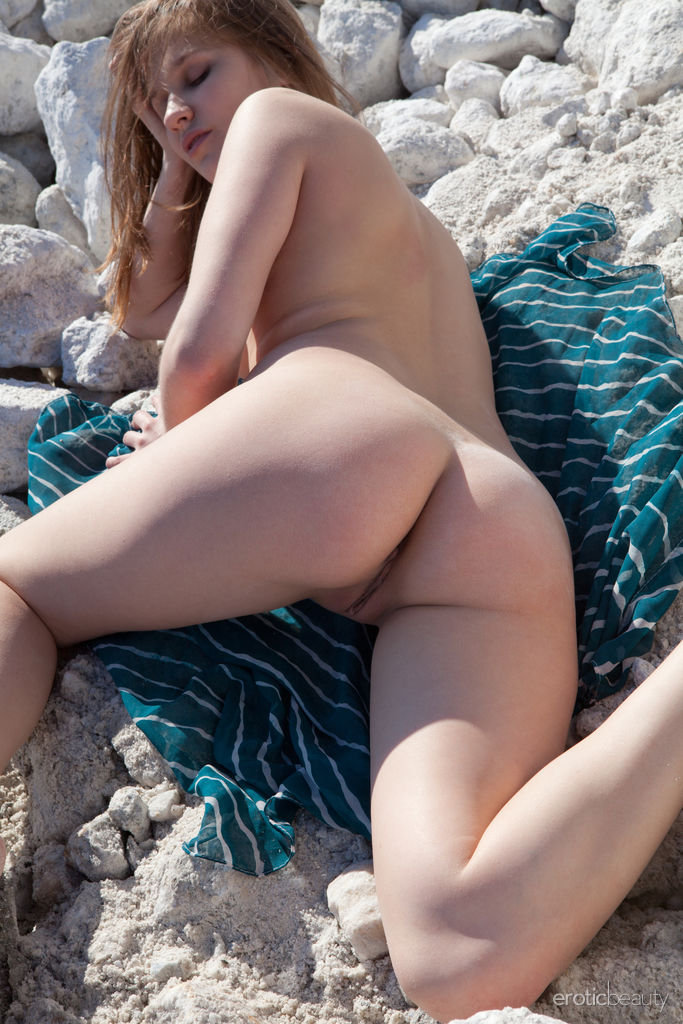 Simona A senta-se nas pedras brancas e exibe sua figura esguia e nua e coochie sem pelos.
