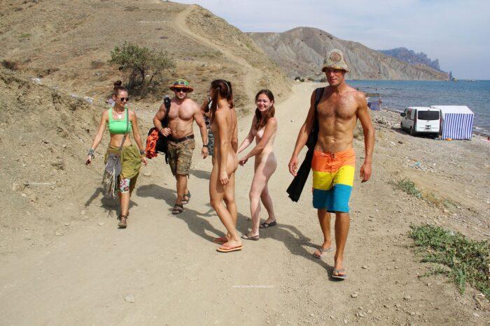 Duas garotas nuas caminham pela mão na praia pública