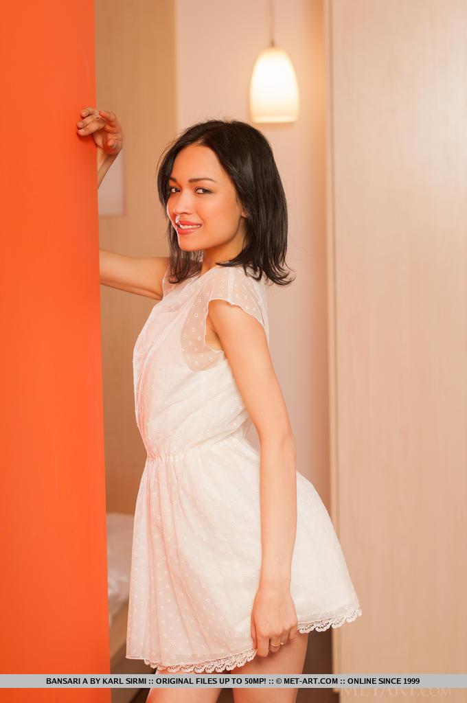 Traços faciais delicados, olhar inocente e corpo pequeno e núbil, Bansari tira seu lindo vestido branco e posa sensualmente dentro do quarto.