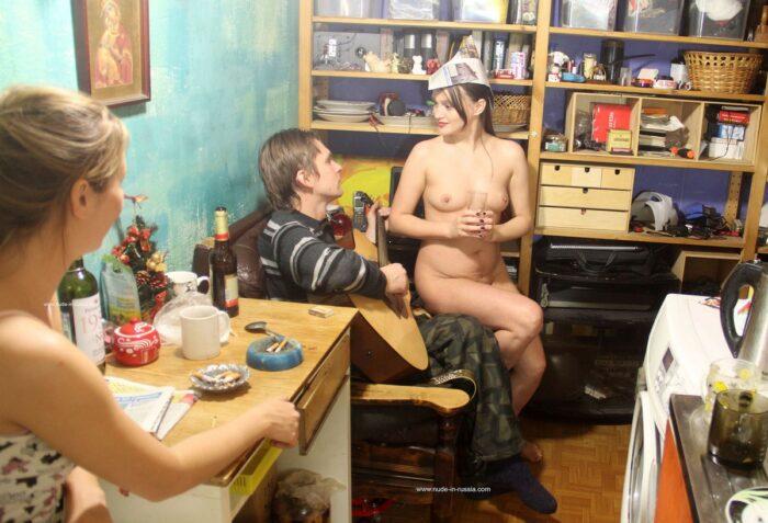 A menina nua Zhenja fuma na cozinha com as amigas