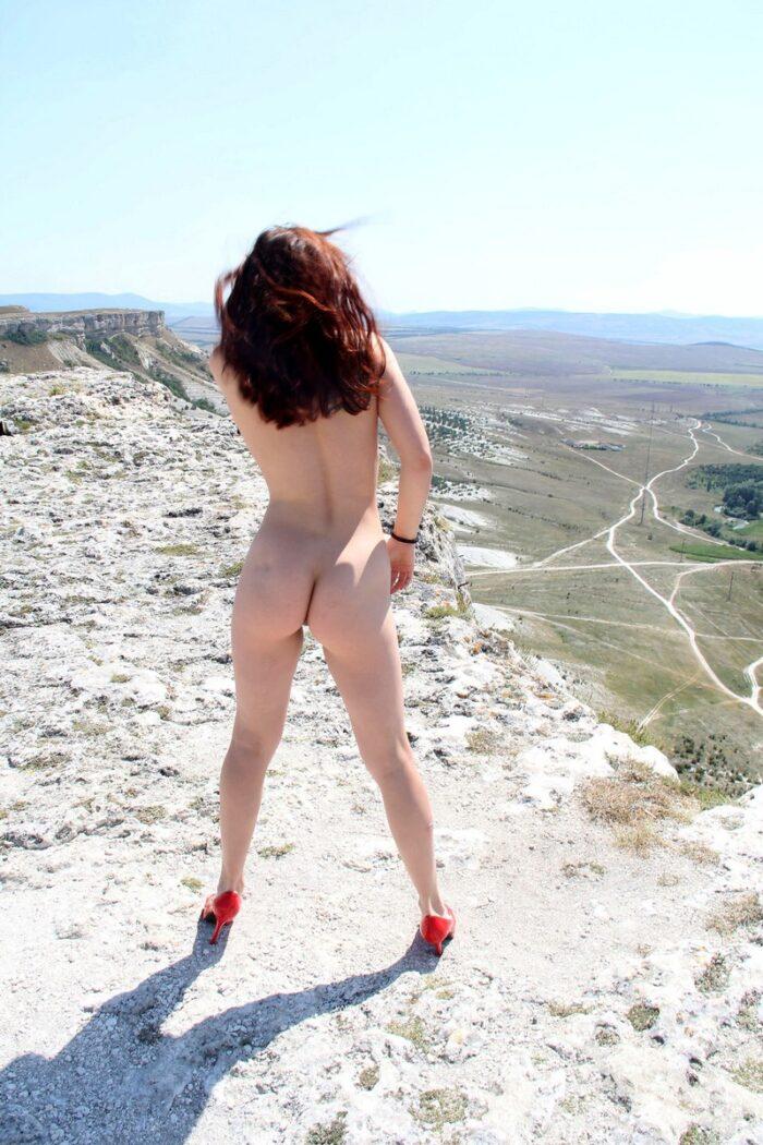 Renara adolescente em sapatos vermelhos em uma rocha íngreme