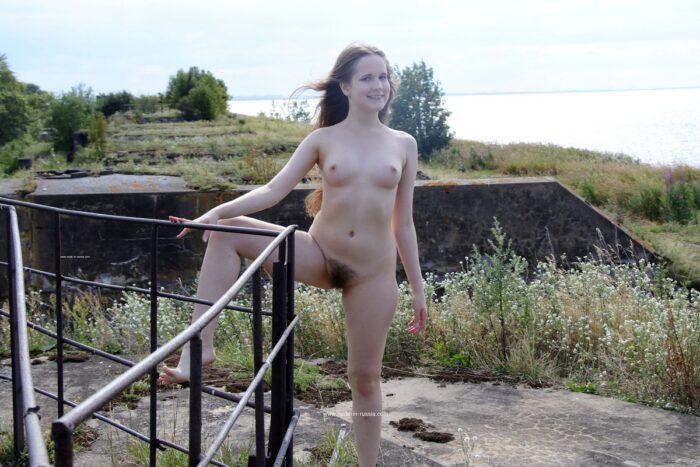 Jovem loira de cabelos compridos com buceta peluda caminhando nua ao ar livre