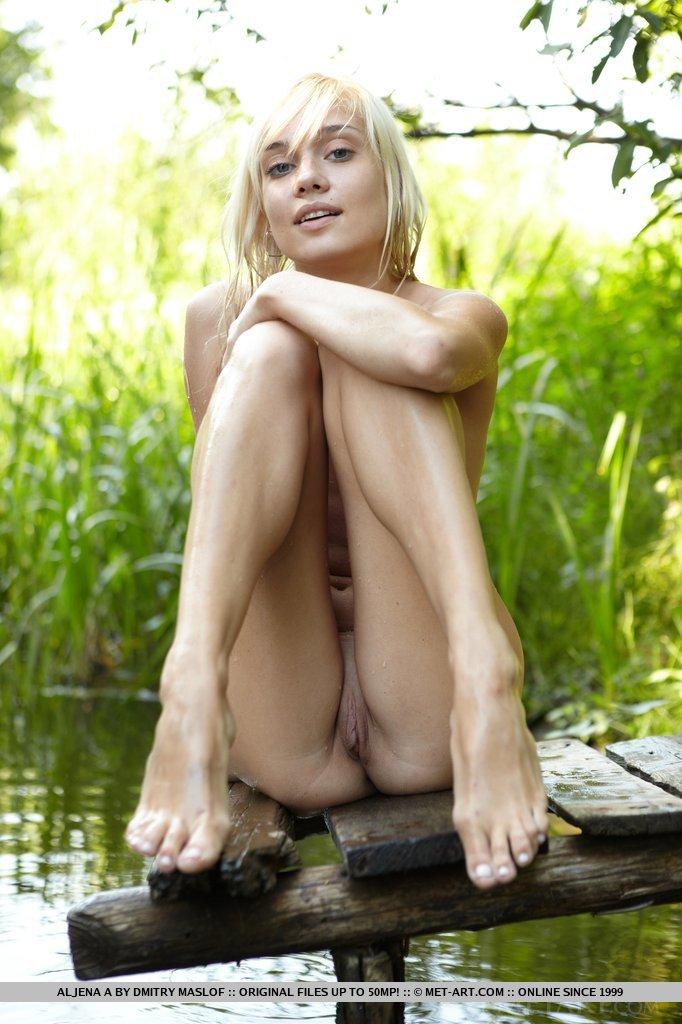 Magnífica localização ao ar livre agraciada por uma deusa sedutora, banhando-se e relaxando desinibidamente entre a grama verdejante, o rio fresco e as árvores nodosas.