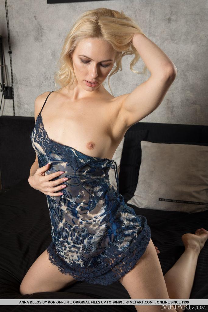 A linda loira Anna Delos deixa sua lingerie de renda azul cair e expor seus pequenos seios empinados, corpo esguio e boceta sem pêlos na cama.