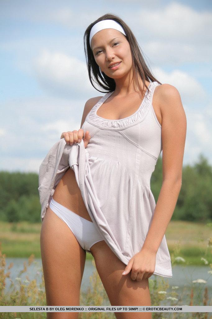 Selesta abre as pernas em poses flexíveis enquanto estreia seu lindo físico atlético em um campo gramado à beira do rio.