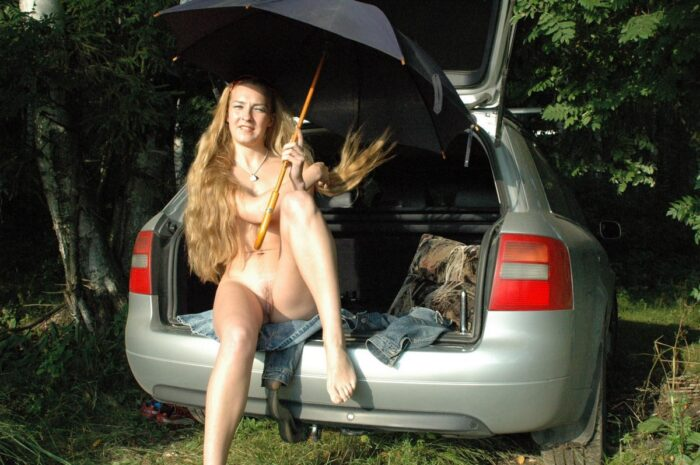 Jovem loira bonita Asja brincando com o vibrador no porta-malas do carro