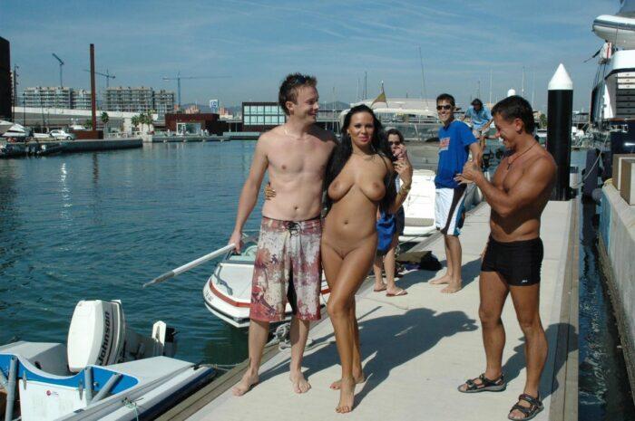 A menina totalmente nua Julia P caminha ao longo do porto da cidade