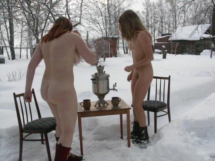 Duas meninas sem roupa tomam chá ao ar livre no inverno