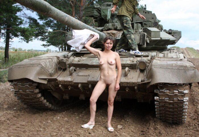 Margarita menina nua com peitinhos em um campo de tanques